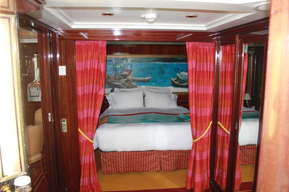 KIng-size bed that is in its own small room that can be closed off with the curtain