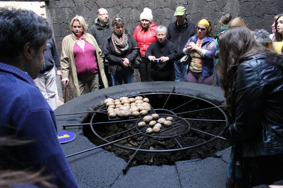 To demonstrate the constant heat, a larger pit was dug with grating placed over it. On the grating are potatoes being roasted. This is to demonstrate how the locals still today have outdoor barbeque pits used for cooking