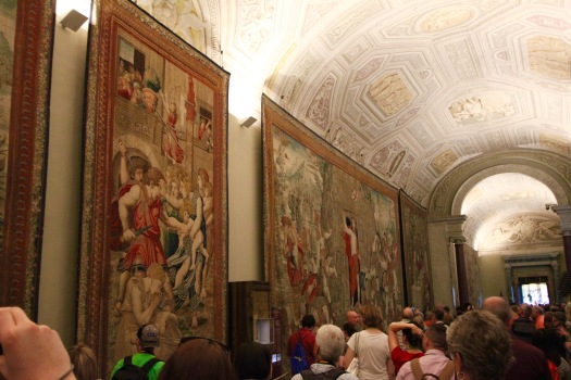 The Gallery of Tapestries in the Vatican Museum. The artwork in the ceiling is flat, but it looks like it is in 3-D. And, along the walls are large tapestries from the 1500s. I left the people in the picture to provide scale to show how large they are. Each one has various religious images woven together.