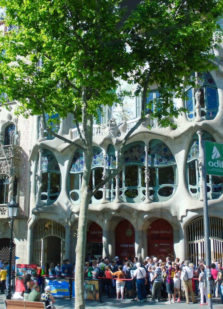 "Stepping back, you can see the ""masks"" in the balconies. The style of Art Nouveau is characterized by curvy lines rather than straight ones, and Gaudi is considered a master at this style."