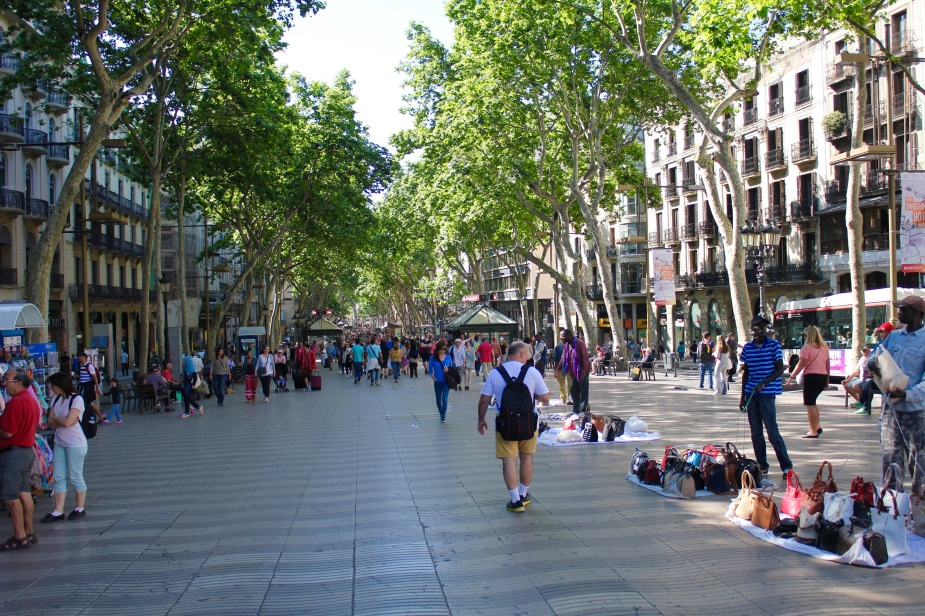 This pedestrian street was lined with vendors selling lots of souvenirs to tourists. This is the part of Barcelona where you have to be very mindful of pickpockets. Notice the guys selling real, genuine fake Prada bags on the right....the bags sit on top of a blanket, and each corner is tied to a rope. The guy stands there with the ropes in his hands, and if he sees the Police, will pull the ropes and all the bags fall into the blanket and he runs off. Admittedly, I waited to watch and see if this would happen, but alas no police.