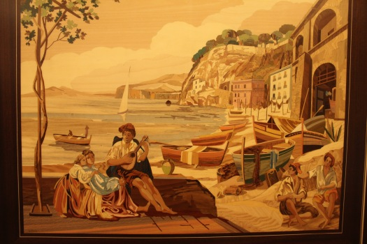 ...this is an example of a finished piece. This is not paint, but various shapes of dyed, thin wood that have been cut out and placed together to form the picture. After it is completed, it is then covered with a glaze to protect it and to give it a shine. The finished pieces are either wall art or is inlaid into the tops of tables or small boxes, etc. It is very fine craftsmanship. To give an idea of cost...this is a wall art piece maybe a 12 inches by 16 inches and it was on sale for $900.
